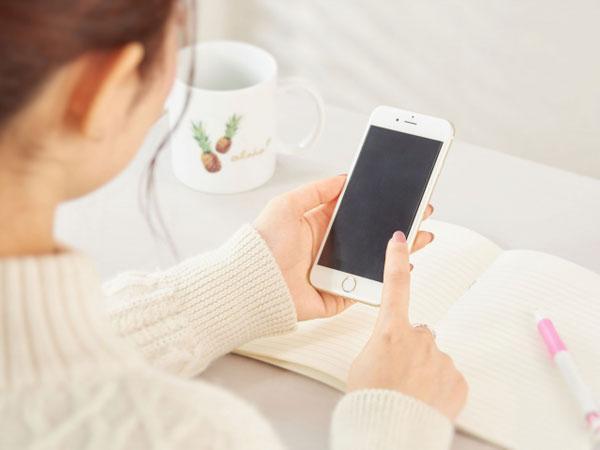 スマートフォンを見る女性の写真